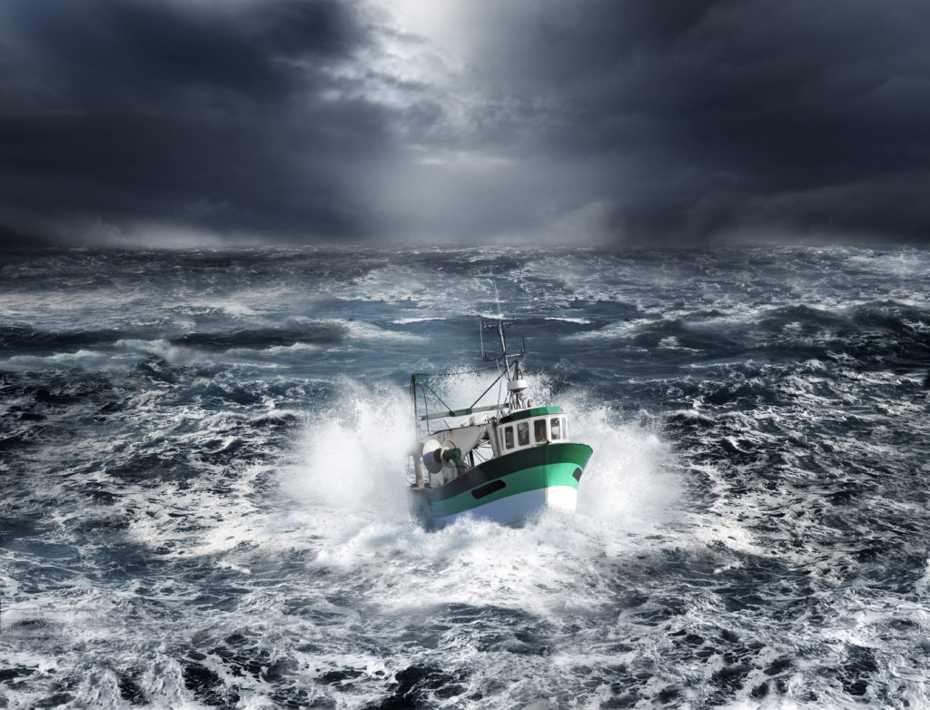 Fishing boat in a storm in the dark, frothy ocean