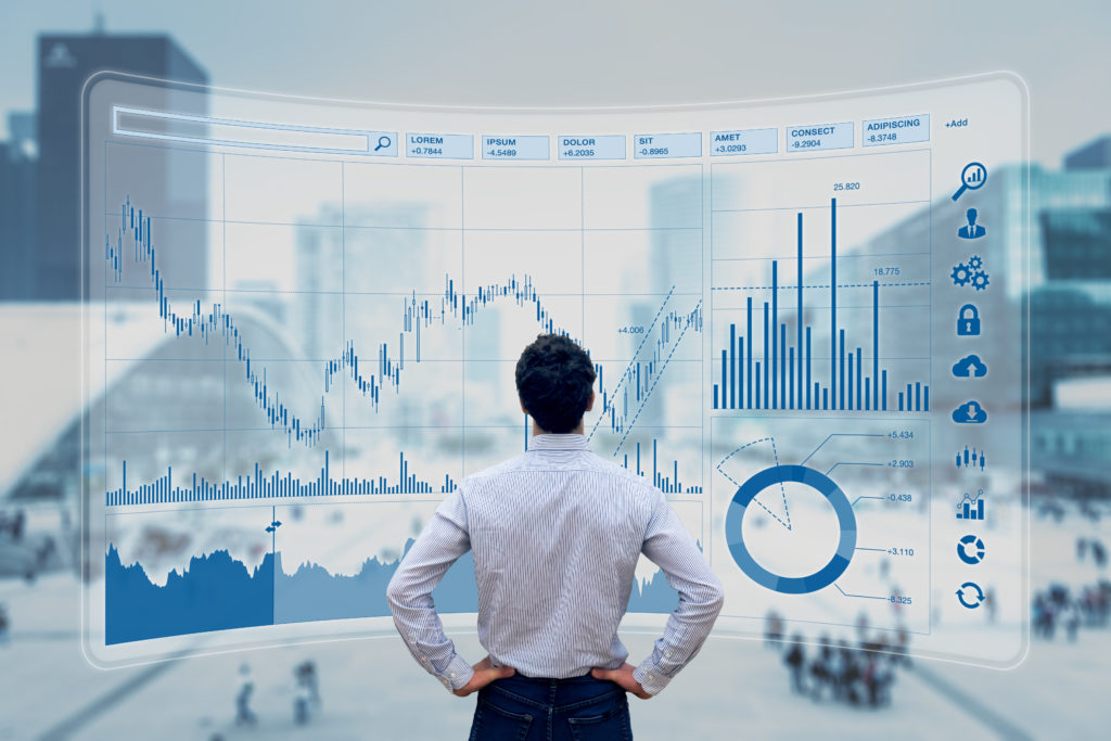 Man standing in front of transparent charts and graphs and examining the figures