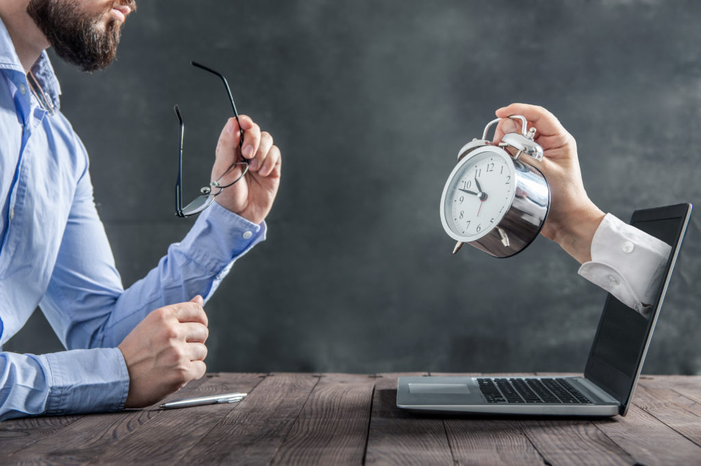 A hand holding an old-fashioned clock extends from a laptop toward a businessman