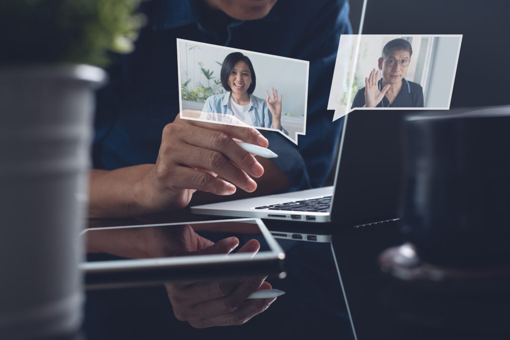 Holographic images of 2 people displayed above a laptop screen