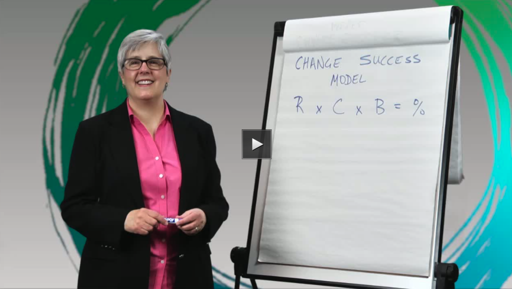 Sue smiling next to a whiteboard with change success formula