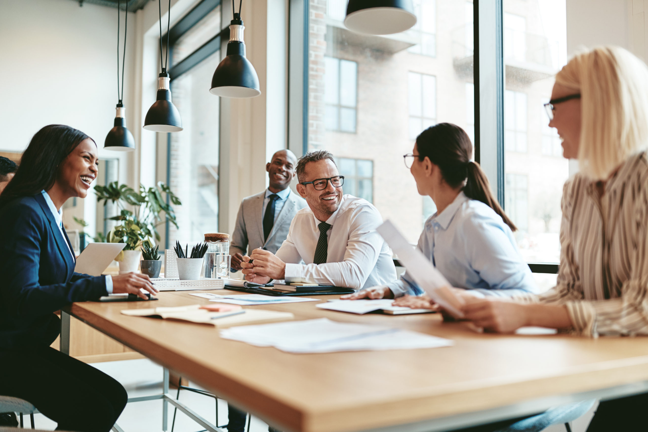 diverse businesspeople meeting around a rectangular conference table